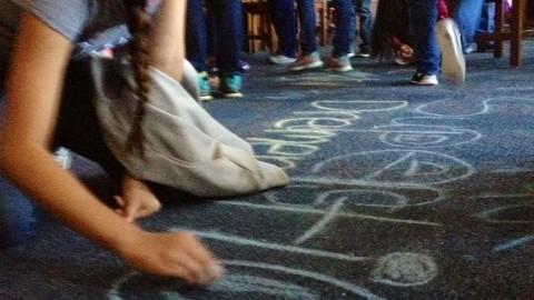 Student writing with chalk on library floor